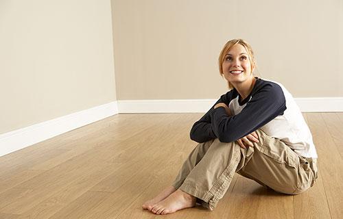 Satisfied water damage repair customer sitting on dry floor
